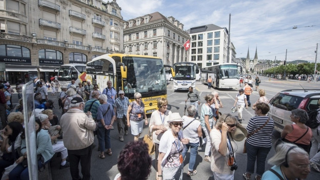 Touristencars parkieren auf dem Schwanenplatz in Luzern und Touristen steigen aus.