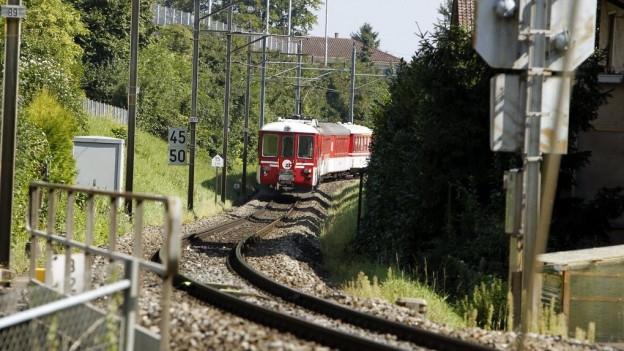 Ein roter Zug fährt in eine Kurve