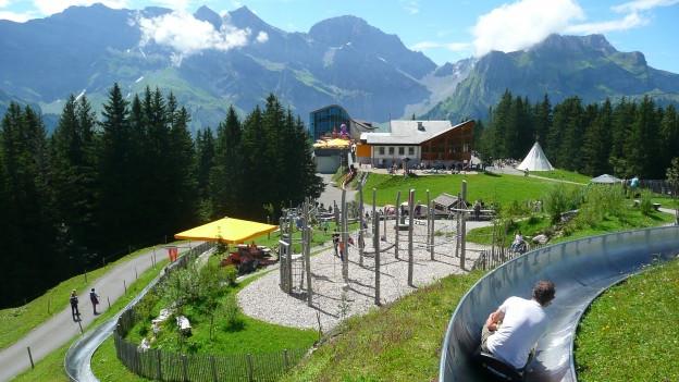 Kinder spielen auf einem Alpenspielplatz.