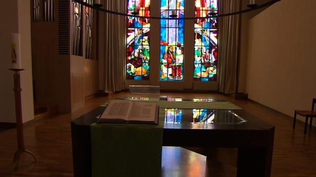 Ein aufgeschlagenes Buch vor einem bunten Kirchenfenster