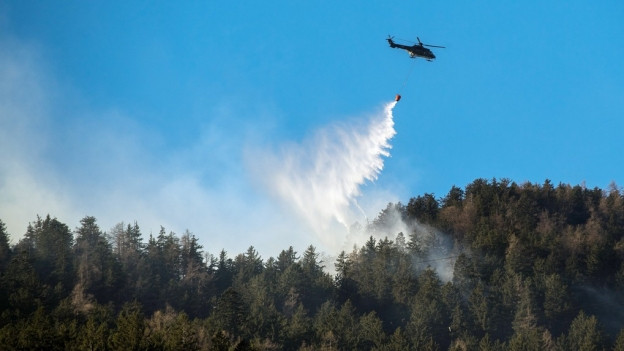 Ein Helikopter hilft bei der Bekämpfung eines Brandes.