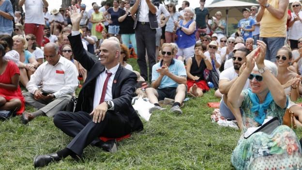 Bundesrat Alain Berset sitzt inmitten von Gästen der Bundesfeier 2018 auf der Rütliwiese.
