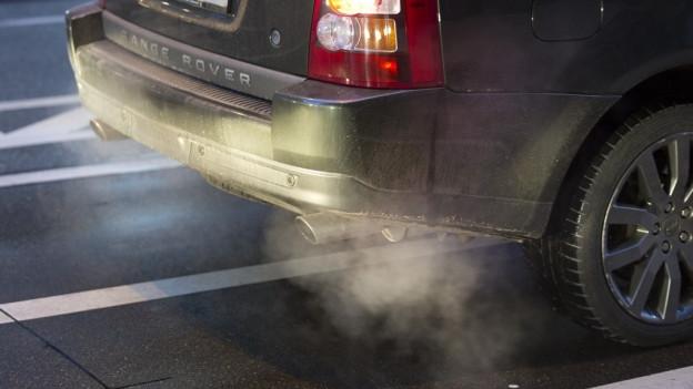 Der rauchende Auspuff eines Autos.