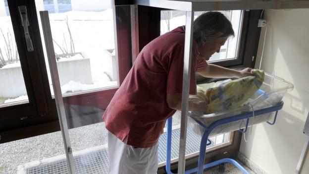 Eine Hebamme am Babyfenster des Spitals Einsiedeln.