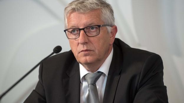 Kurt Sidler, Präsident des Raiffeisen-Verbands Luzern, Ob- und Nidwalden, sitzt an einer Medienkonferenz vor einem Mikrofon.