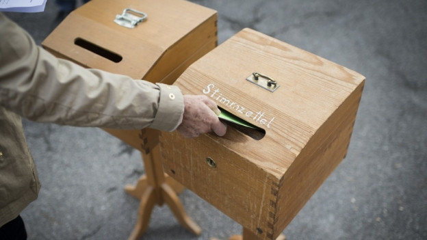 Eine Person wirft ihren Wahlzettel in die Urne.