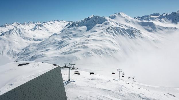 Eine Gondelbahn fährt einen verschneiten Berghang hoch.
