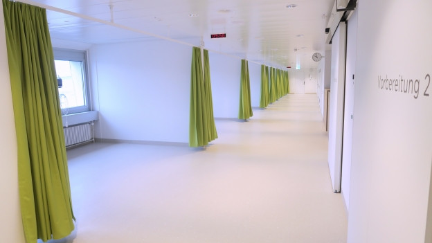 Ein weisser Raum mit grünen Vorhängen.