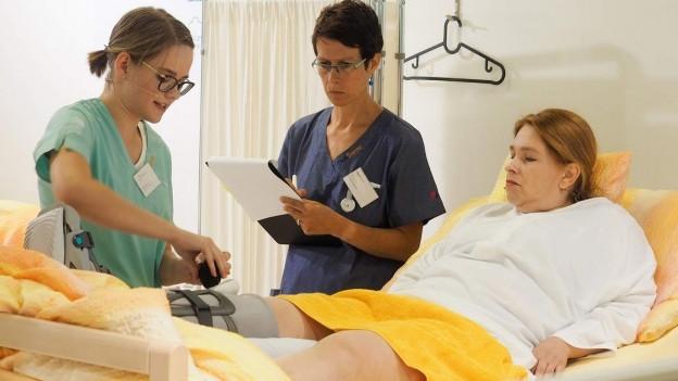 Eine Pflegefachperson wird während der praktischen Ausbildung am Krankenbett begleitet.