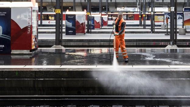 Ein Mann reinigt die Perrons im Bahnhof Luzern.