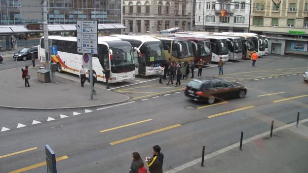 Mehrere Cars stehen auf dem Löwenplatz in Luzern.