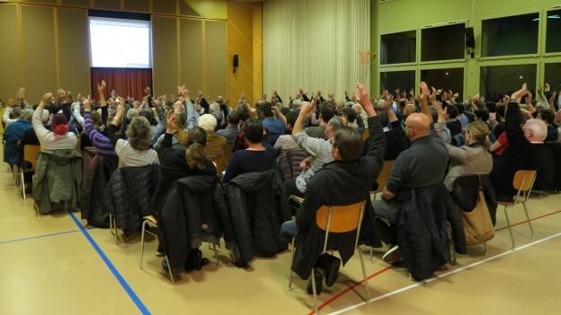 Turnhalle in der Luzerner Gemeinde Wikon. Auf mehreren Stuhlreihen vor einem Rednerpult sitzen die Stimmberechtigten.