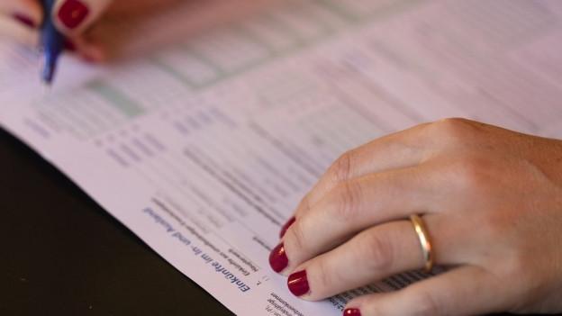 Frau füllt Steuererkärung aus