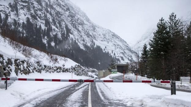Blick auf eine Barriere, die die Sperrung der Strasse zwischen Hospental und Realp signalisiert.
