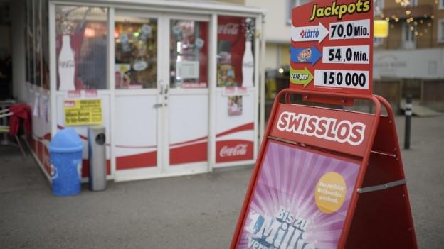 Ein Schild vor einem Kiosk wirbt dafür, beim Zahlenlotto mitzumachen.