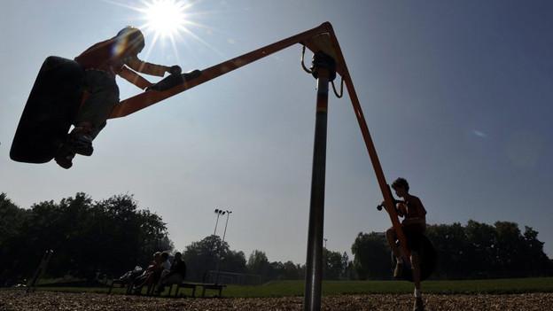 Zwei Kinder spielen auf einer Schaukel.