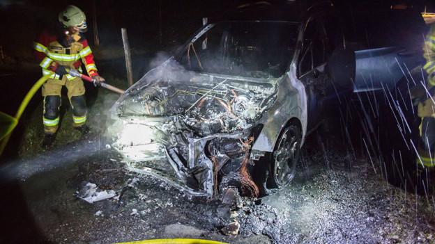 Mitglieder der Freiwilligen Feuerwehr der Stadt Zug löschen ein brennendes Fahrzeug.