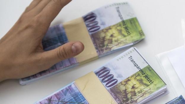 Eine Hand greift nach Geldscheinen.