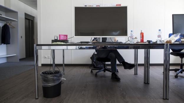 Blick in ein modernes Büro mit einem Mann am Computer.