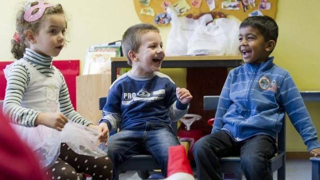 Ausländische Kinder sitzen in einer Spielgruppe im Kreis.