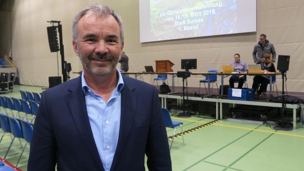 Der Surseer Stadtpräsident Beat Leu steht in der Stadthalle - bald werden sich die Stuhlreihen hinter ihm füllen.