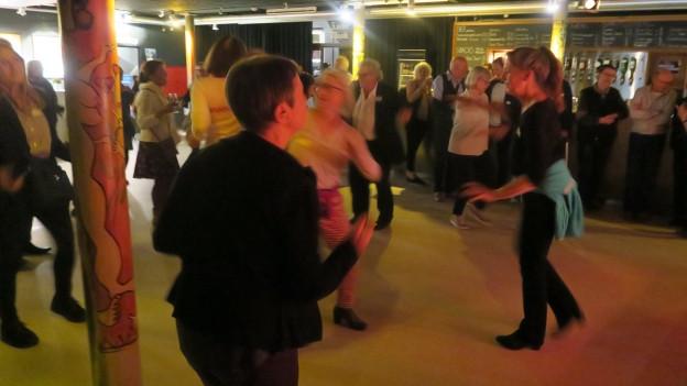 Tanzende Menschen im schummrigen Licht.