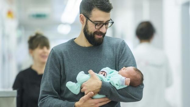 Junger Vater mit einem Kind auf dem Arm: Der Kanton Luzern will nicht vorpreschen in Sachen Vaterschaftsurlaub.