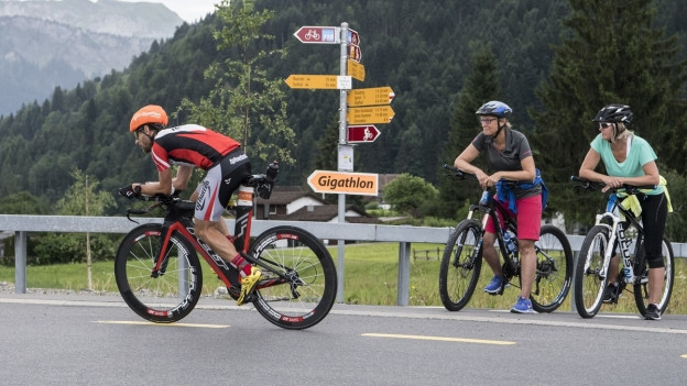 Ein Biker fährt an einem Schild mit der Aufschrift Gigathlon vorbei.