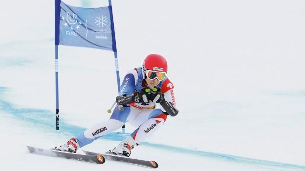 Ein Schweizer Skifahrer fährt die Piste hinunter.