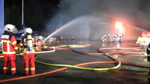 Die Feuerwehr bekämpft den Brand in der Bootswerft.