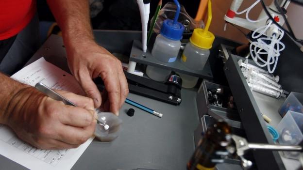 Symbolbild Drogentest: Hände analysieren eine Pille