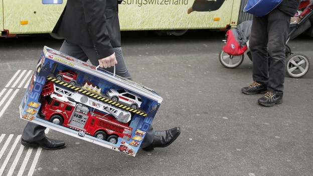 Ein Mann läuft mit einem gefkauften Spielzeuglöschfahrzeug durch eine Strasse.