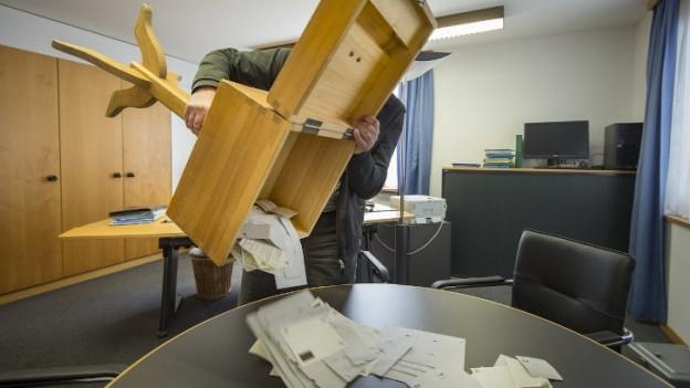 In einem Urnenbüro leert ein Stimmenzähler die Wahlzettel aus einer Urne zum Auszählen auf einen Tisch.