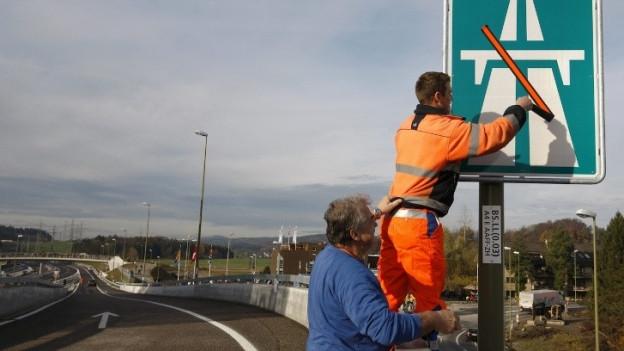 Ein Arbeiter montiert ein Autobahnschild