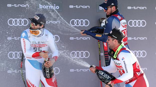 Zwei Skifahrer überschütten ihren Kollegen mit Schaumwein.