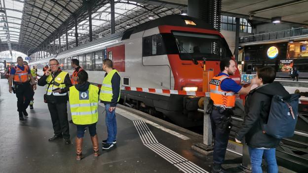 Ein Zug im Bahnhof Luzern, Polizisten, SBB-Mitarbeitende