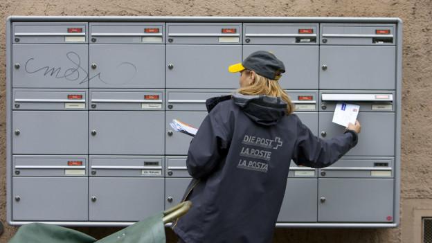 Eine Briefträgerin schiebt einen Brief in einen Briefkasten eines Mehrfamilienhauses. Sie steht mit dem Rücken zur Kamera.