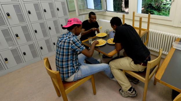 Asylsuchende beim Essen in einer Unterkunft.