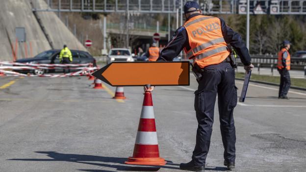 Ein Polizist steht auf der Autobahn am Gotthard und hält Autos an