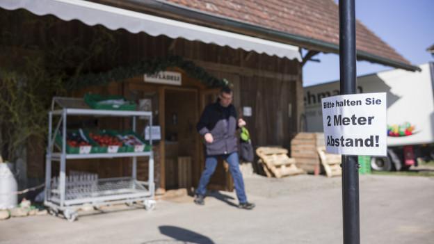 Hofladen mit Schild 2 Meter Abstand halten