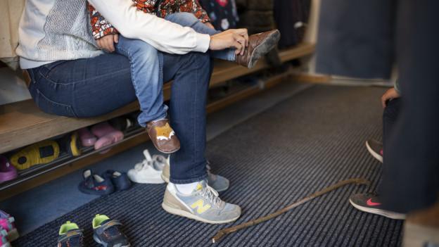 Ein Kind zieht in der Kita die Schuhe an