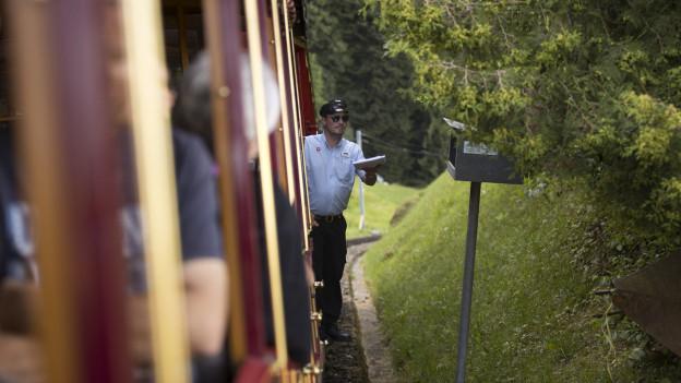 Mann der Rigibahnen lehnt aus Waggon
