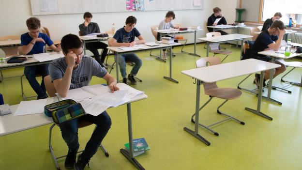 Schüler sitzen an Pulten