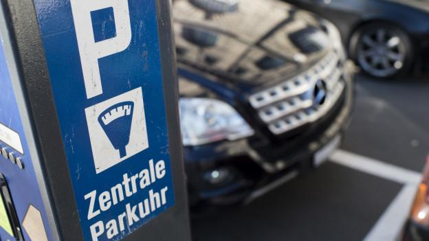 Eine Parkuhr auf einem Parkplatz, dahinter ein Mercedes