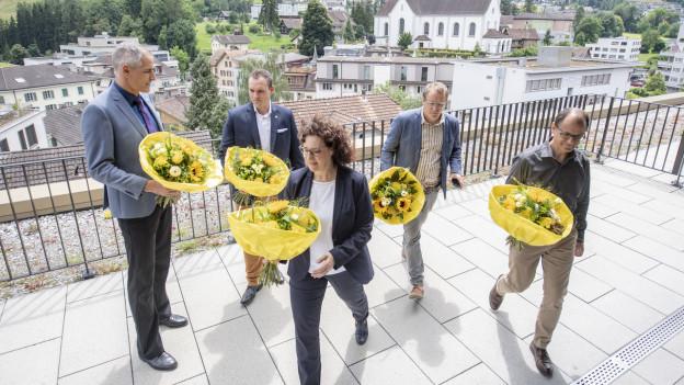 fünf Menschen mit Blumensträussen auf Flachdach