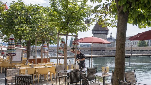 Restaurant-Mitarbeiter in Luzern richtet Tische.