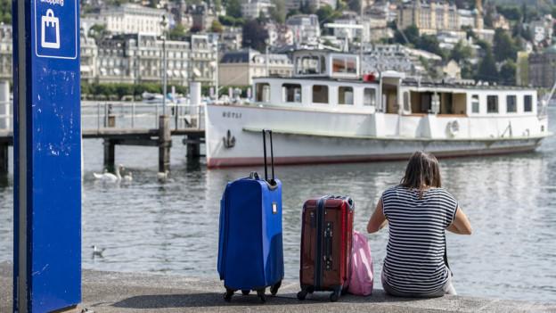 Frau sitzt mit Koffern am Seeufer.