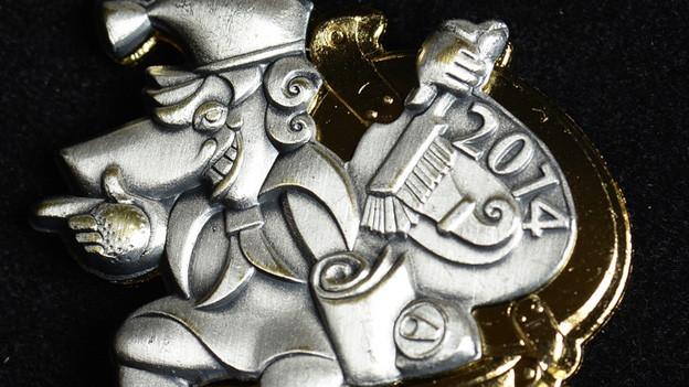 """Die Fasnachtsplakette 2014 symbolisiert das Motto """"gäll, bliib suuber!"""""""
