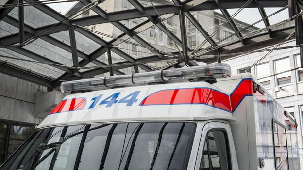 Eine Ambulanzfahrzeug steht vor einem Spital.