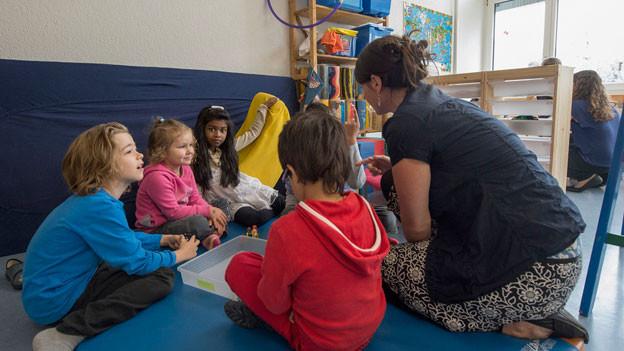 Eine Lehrerin im Unterricht, umgeben von Schülern.